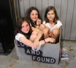 3 girls stuffed themselves into the wooden lost and found box. Smiling at the camera.